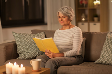 age, leisure and people concept - happy senior woman reading book at home in evening