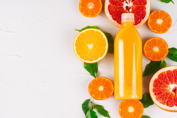 Deurstickers Sap Glass bottle of orange juice with halves of ripe oranges