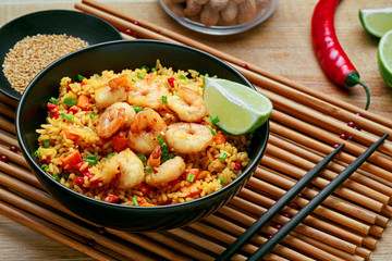 Delicious fried rice with shrimps, lime and vegetables in a black bowl on a bamboo placemat. Traditional Asian food on a wooden table.