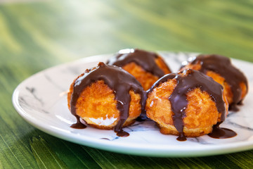 Fototapete - Profiterole with vanilla and chocolate sauce