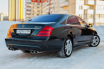 Rear view of a Mercedes Benz business class bumper and trunk of a car, a long black limousine, amg model outdoors, prepared for sale on a sunny winter day with a polished shiny body.