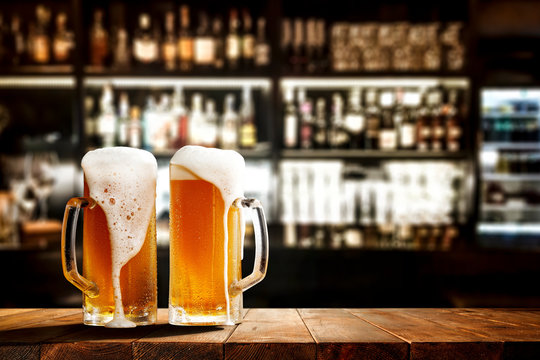 Glass of beer on wooden board and blurred bar background.Free space for your decoration.