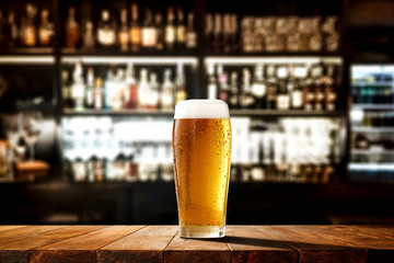 Printed roller blinds Alcohol Glass of beer on wooden board and blurred bar background.Free space for your decoration.