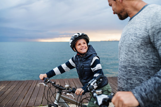 Father and small son with bicycles outdoors standing on beach.