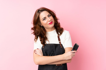 Young Russian woman over isolated pink background with hairdresser or barber dress and holding hair cutting machine