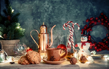 Christmas treat with hot coffee cookies and candies. Festive card with snowman and new year decoration on wooden board in rustic style.