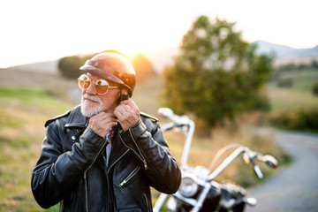 A senior man traveller with motorbike in countryside, putting on helmet. Wall mural