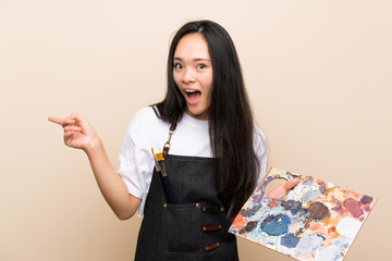 Teenager painter asian girl surprised and pointing finger to the side