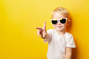 Portrait of cheerful little boy in a white t-shirt wearing sunglasses and looking away on orange background showing two fingers peace sign Fototapete