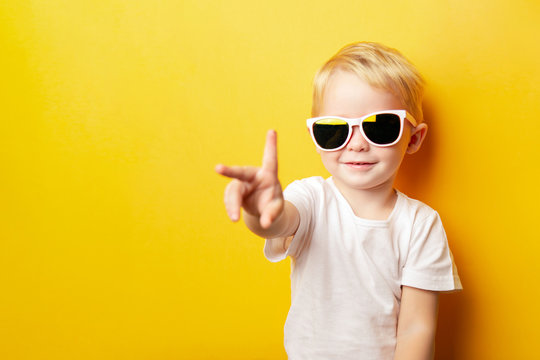 Portrait of cheerful little boy in a white t-shirt wearing sunglasses and looking away on orange background showing two fingers peace sign