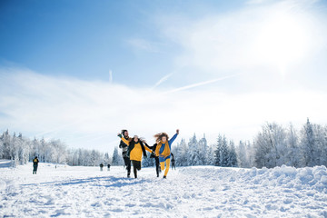 Group of young friends on a walk outdoors in snow in winter forest, running.