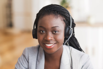 Portrait of friendly afro female customer service operator in headset