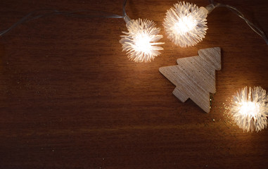 New Year's decoration. glowing garlands and wooden figurines on a wooden background.