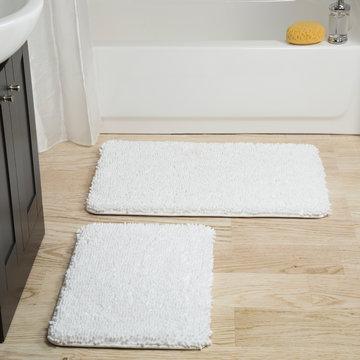 white cotton bath mat over wooden floor