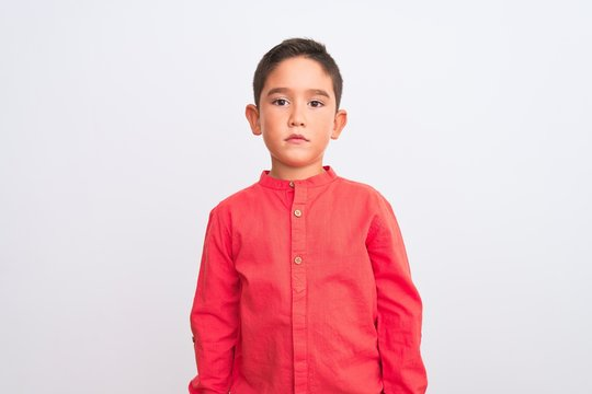 Beautiful kid boy wearing elegant red shirt standing over isolated white background Relaxed with serious expression on face. Simple and natural looking at the camera.
