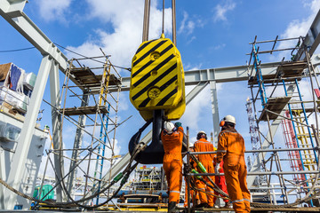 Offshore workers performing inspection to a crane hook and rigging arrangement prior to heavy lift