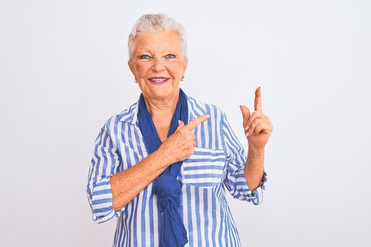Senior grey-haired woman wearing blue striped shirt standing over isolated white background smiling and looking at the camera pointing with two hands and fingers to the side.