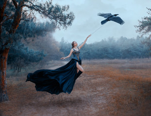 Conceptual photo of slavery and freedom. Black raven pulls woman hand in sky. Dark gothic sexy queen in luxury chic dress. Long train flutters waving in flight. Art levitation. Backdrop cold forest