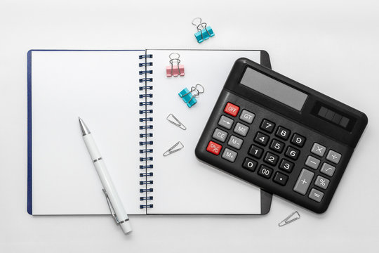 Notebook with pen and calculator on white background.