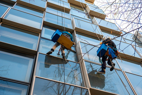 Workers washes windows of a building hanging on a ropes.