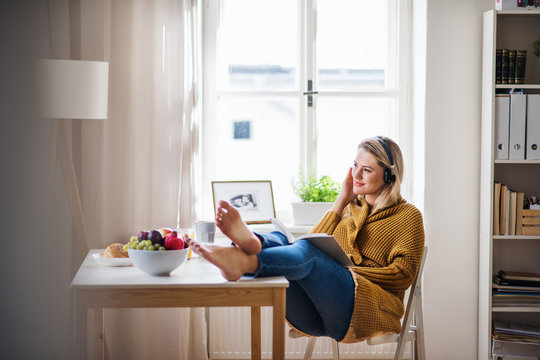 Young woman sitting at the table indoors at home, reading a book.