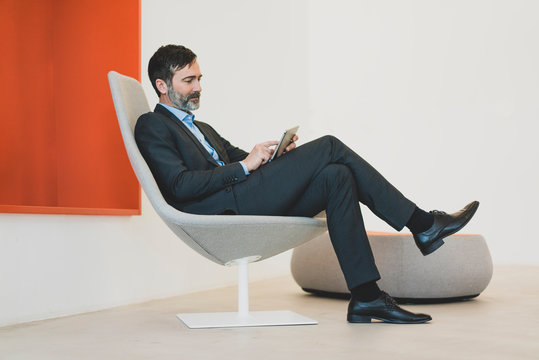 Mature businessman sitting in chair using tablet