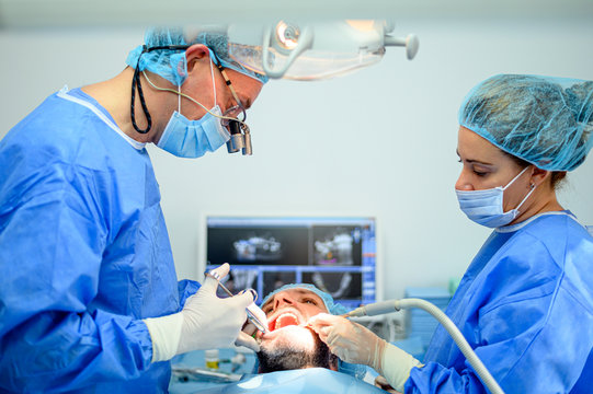 Dental surgeon and assistant work putting dental implant
