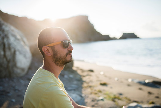 Man with sunglasses on the beach at backlight