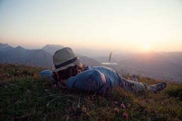 Austria, Tyrol, Unterberghorn, man relaxing on alpine meadow at sunset