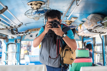 Young Thai male traveller taking a photo with dslr camera on bus while travelling.