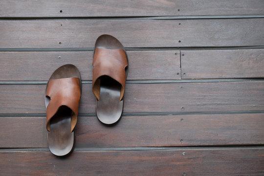 brown Italian sandals over a wooden deck