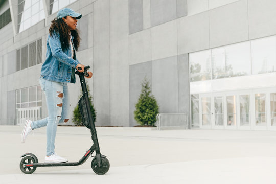 Young black woman riding scooter in urban city