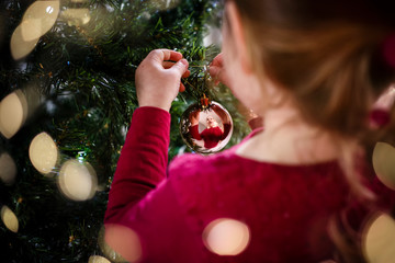 Festive image of girl decorating Christmas tree reflection in bauble