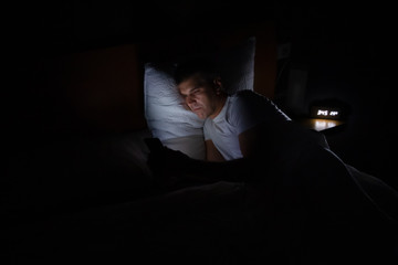 A man is lying in bed in total darkness looking at his smart phone