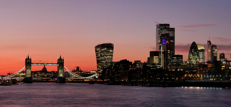 Panoramic view of Tower Bridge framing St. Paul's Cathedral with the City tower blocks at sunset, London