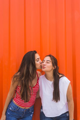 Best friends kissing against orange wall