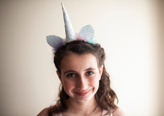 Close up of girl 10-12 years old smiling with unicorn headband on