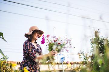 happy woman picking flowers in an urban garden