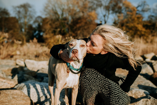 woman kissing dog on the beach