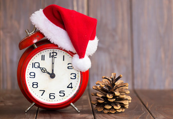 Christmas time concept, red santa hat alarm clock and pine tree cone on a brown wooden background