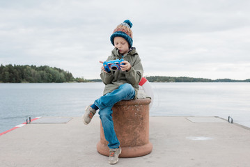 young boy sitting by the beach looking at his pictures on his camera