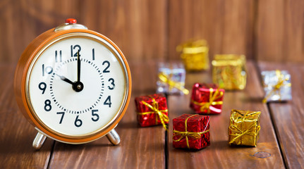Time to gift, christmas shopping concept, orange retro alarm clock and gift boxes on wooden background, web banner