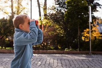 young boy stood in a street looking through binoculars