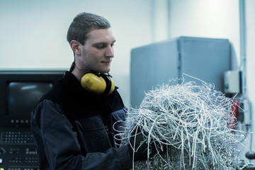 engineer in a workshop with metal stripes