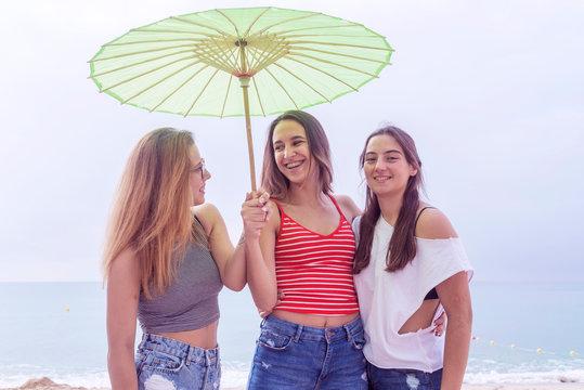 Happy young women having fun on a beach under umbrella