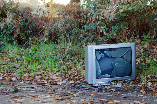 Old gray CRT television smashed and dumped at the side of the road in Coruna Spain