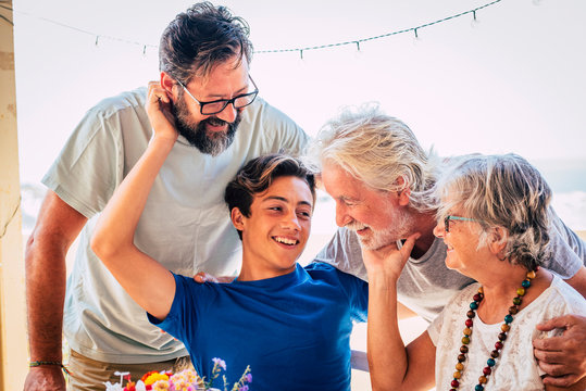 Family caucasian portrait of happy cheerful family with three generations from grandson to son and grandfathers all together having fun and love - concept of mixed ages and friendship