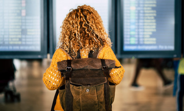 Blonde curly lady with backpack viewed from back looking the display with flights and timing at the airport - travel lifestyle and wanderlust activity - deleted flight concept
