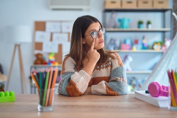 Young beautiful teacher woman wearing sweater and glasses sitting on desk at kindergarten Pointing...