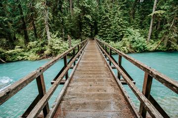 A pedestrian bridge crosses a vibrant blue river, cascades, washington
